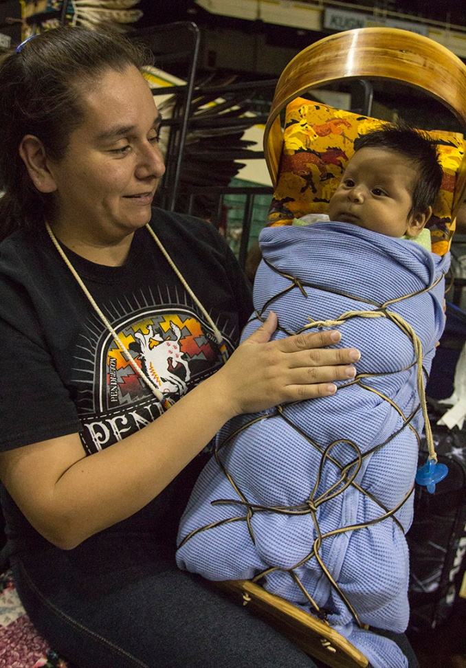 Michelle Littlesinger, from the Yakama tribe, holds her 7-week-old son, Ezrah, in the crowd on the first day of the 49th Annual UO Mother's Day Powwow. Littlesinger considers herself on maternity leave from dancing, but has been helping out by braiding hair.