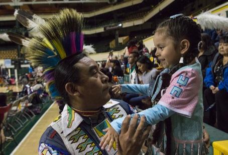 Fernando Littlesinger, a Navajo from Window Rock, Arizona, embraces his daughter, Myrcene, shortly before she steps onto the floor for the jingle dress dance.