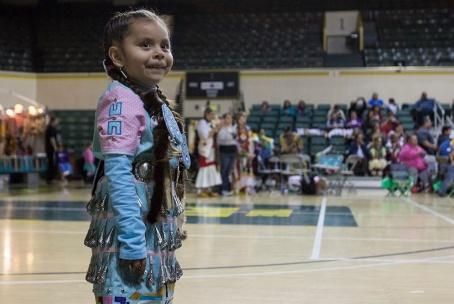 Myrcene glances back with a smile at her parents before she begins her jingle dress dance.