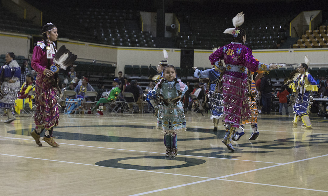 During her jingle dress dance, Myrcene looked toward her parents in the bleachers. Her mother, Michelle, says that this dance sounds like rain on a tin roof. The cones on the jingle dress are often made from Copenhagen tobacco lids, pierced, shaped and sewn onto the dress.